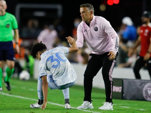 Inter Miami head coach Phil Neville helps DC United midfielder Kevin Paredes (30) stand up on June 9, 2021