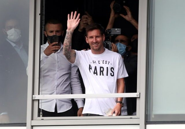Lionel Messi waves when he arrives in Paris on August 10, 2021