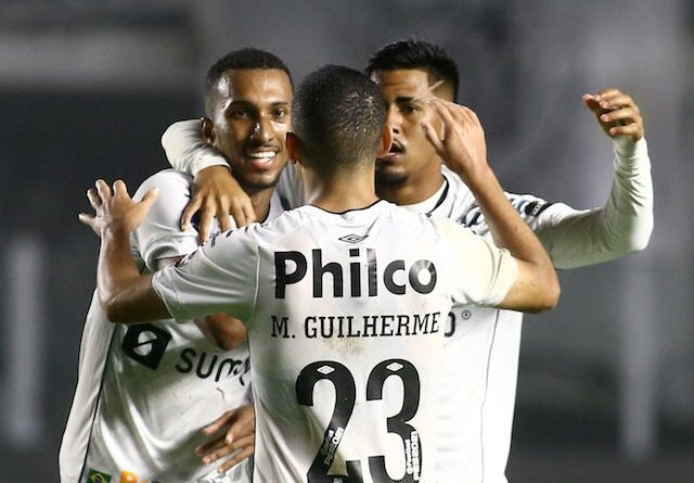 Santos's Lucas Braga celebrates with his teammates after an own goal by Libertad and Santos' second on August 13, 2021